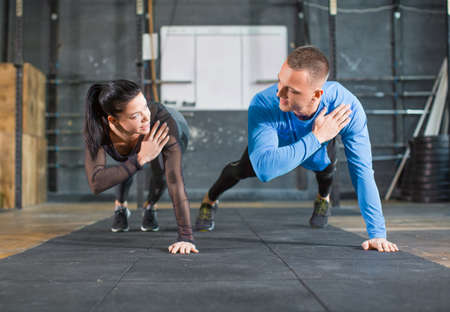 Fitness couple strengthen hands at fitness training. Man and woman working out in gym