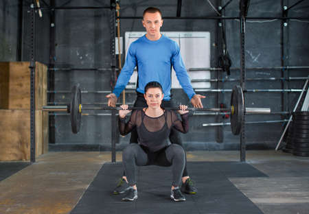 Personal trainer helps woman work with barbell at squat exercises In gym. Front view Stok Fotoğraf