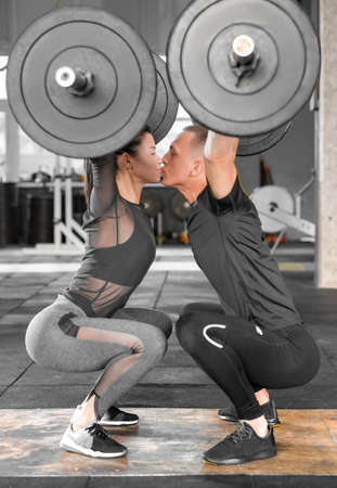 Fitness couple making a Barbell Jerk and kissing. Sporty family in gym