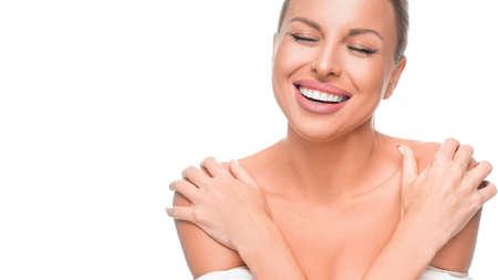 Happy laughing woman enjoying in her healthy skin. Woman touching her shoulders Фото со стока