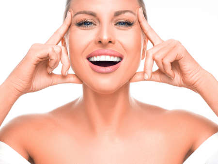Happy laughing woman enjoying in her healthy skin. Woman touching her face.