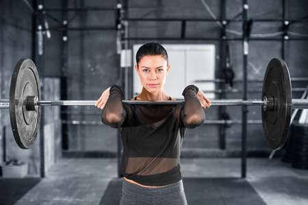 Powerlifter femminile che fa un pulito e uno scatto con pesi pesanti. Ritratto ravvicinato