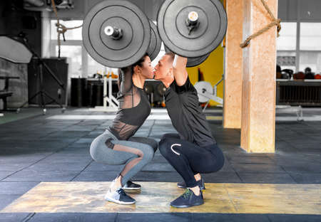 Fitness couple making a Barbell Jerk and kissing each other. Sporty family in gym. Stok Fotoğraf