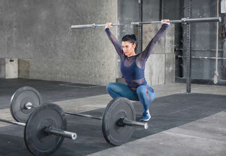 The athletic young woman is doing the exercise split jerk with barbell. Front-side view. Stok Fotoğraf