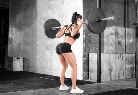 Side view of a woman in the gym. Squats