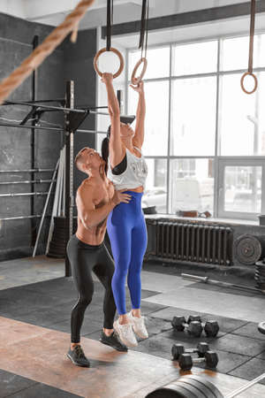 Trainer help athletic woman pulling up on the gymnastic rings in the gym. Healthy lifestyle concept