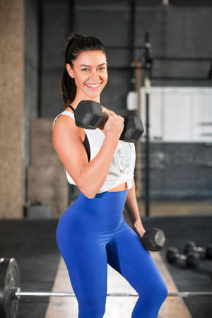 Portrait of a smiling woman with dumbbell in gym.