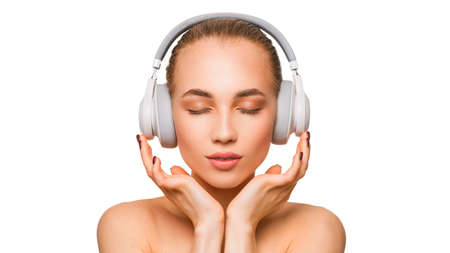Beautiful woman in headphones listening to the music with closed eyes.
