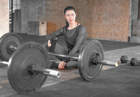 Tired woman sitting in a gym on the floor with barbells. Healthy lyfestyle concept