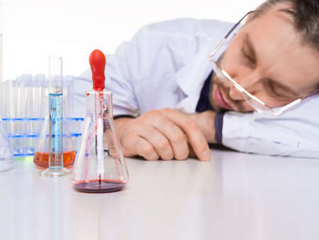 Exhausted scientist sleeping in laboratory. Science and experiment in lab theme.
