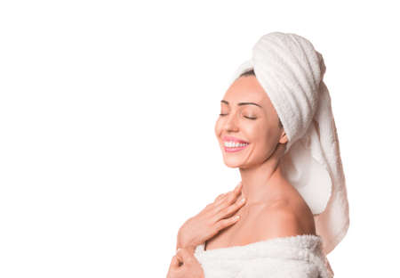 Spa skincare beauty woman drying hair with towel on head after shower treatment. Beautiful smiling woman touching soft skin with closed eyes isolated on white background.