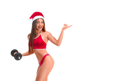 Portrait of young, sexy and beautiful woman in sport suit and Santa hat. Girl in underwear lingerie with dumbbell. Woman showin on your product.