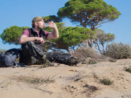 Tourist man drinking water from the plastic bottle during break in a desert walk.