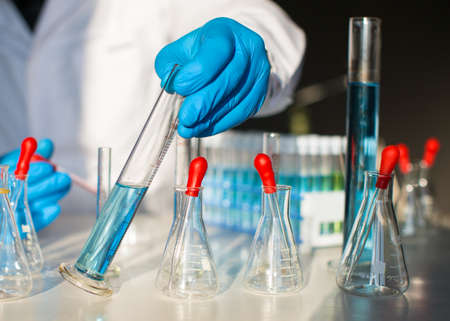 Researcher looking on blue liquid substance in test tube.