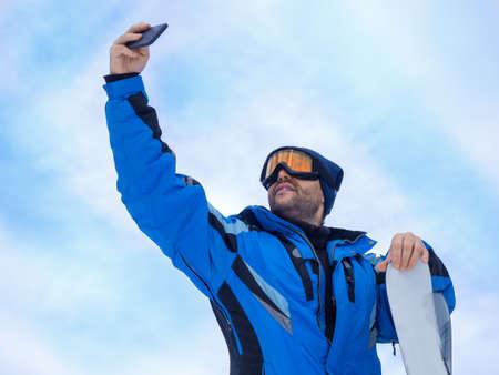 Man with a ski make a selfie over sky bacground.