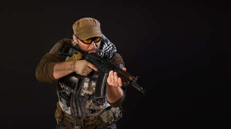 Soldier mercenary with a gun aiming at the enemy. Photo on a dark background. Archivio Fotografico
