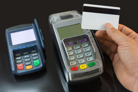 A male hand holds a payment card above the payment terminal.