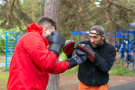 Middle-aged boxer training with coach.