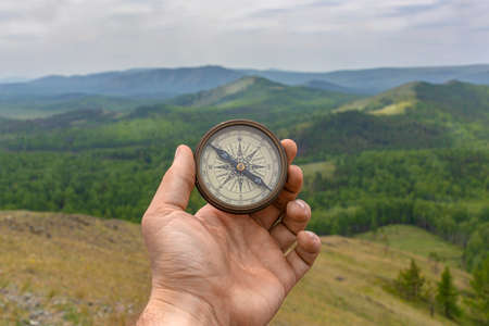 Male hand is holding a magnetic compass on the background of hills and the sky.