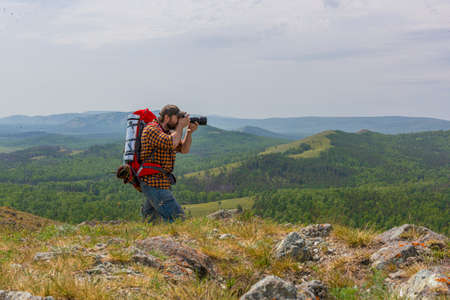A photographer with a large backpack takes a photo.