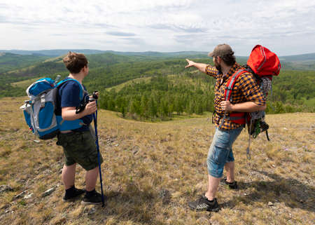 Father and son travel in nature, hiking in mountain. Father showing somtehing by hand. Back view.