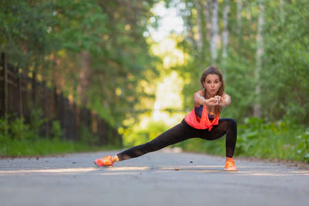 Sport and healthy lifestyle concept - woman stretcing muscles. Standard-Bild