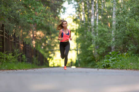 Sportswoman runs along the road in the forest.