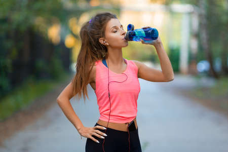 Woman athlete drinks water on the street after the race. Standard-Bild - 149469890