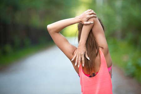 スポーツと健康的なライフスタイルの概念 - ワークアウトの前に筋肉を温める女性。バックビュー,