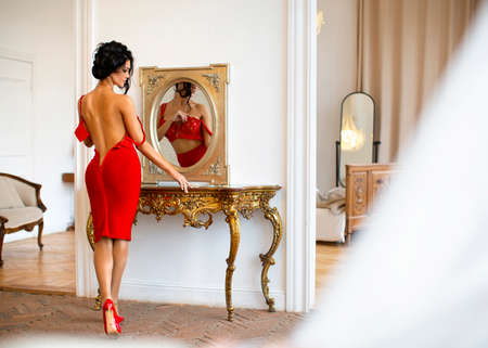 A sexy woman in a bedroom dresses in a red dress in front of a mirror before going to a social event.