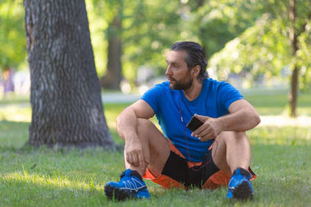 Middle-aged man having rest after workout outdoor. Listening to the music via earphones. Standard-Bild - 149469904