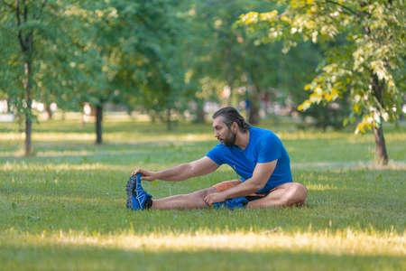 Man stretches outdoor in summer time. Standard-Bild - 149273521