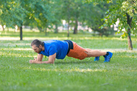 Bearded middle aged man in plank position outdoor.