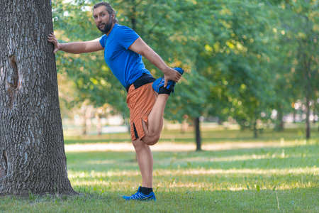 Man warming up muscles before jogging outdoor in summer time.