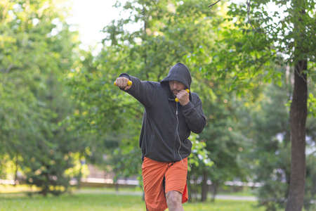 Middle aged fighter man in public park. Boxing practice. Standard-Bild - 149163647