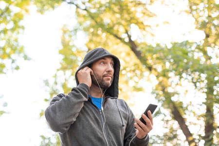 Man inserts earphones into ears before running training Standard-Bild