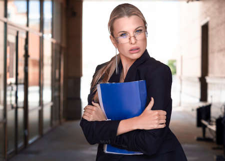 Businesswoman in eyeglasses tightly holds a folder with important documents and incredulously looks at the camera. Standard-Bild - 149950545