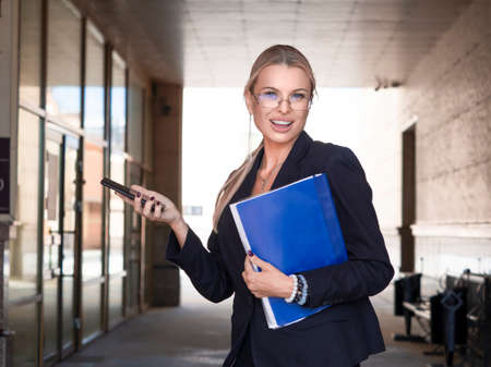 Close portrait of a woman in a business suit looking at camera, smiling and holding mobile phone. Standard-Bild - 149950547