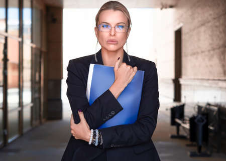 A close portrait of a woman in a business suit holds tightly a folder with documents and looks incredulously at the camera. Standard-Bild - 149950548
