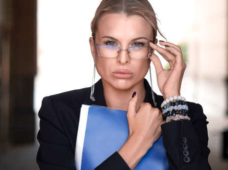 Businesswoman or lawer tightly holds the document folder, adjusts her eyeglasses and incredulously looking at the camera. Standard-Bild - 149950549