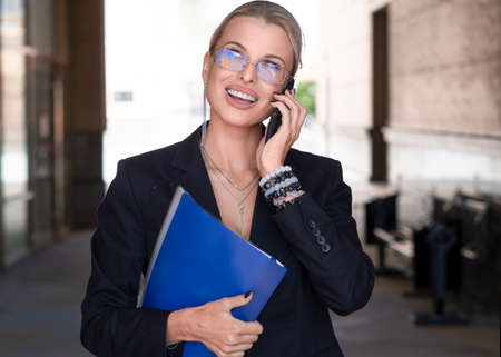 Portrait of a smiling businesswoman talking phone outdoor.