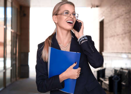 A woman in a business suit carries a folder with documents and smiles while talking on the phone.