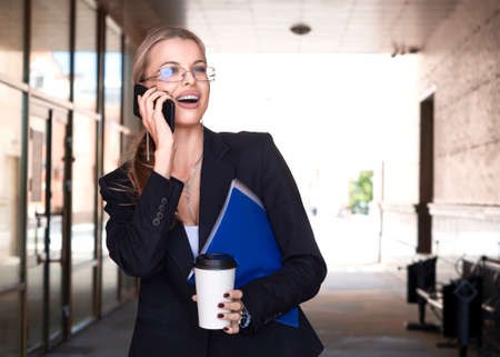 Close portrait of a woman in a business suit smiling talking phone. Standard-Bild