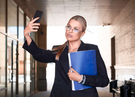Beautiful business woman in eyeglasses takes a selfie, standing on the street with a folder in her hands. Business concept. Standard-Bild - 149950554