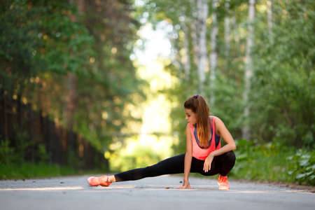 Woman warming up muscles before jogging. Sport and healthy lifestyle concept. Standard-Bild - 150011971