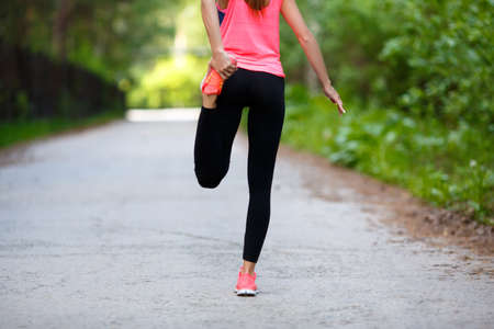 Sport and healthy lifestyle concept - jogger woman stretcing muscles. Standard-Bild