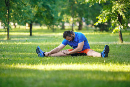 Man stretches outdoor in summer time.