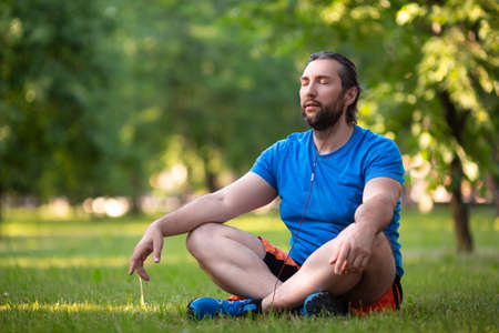Middle aged bearded man in lotus pose outdoor. Standard-Bild - 150068954