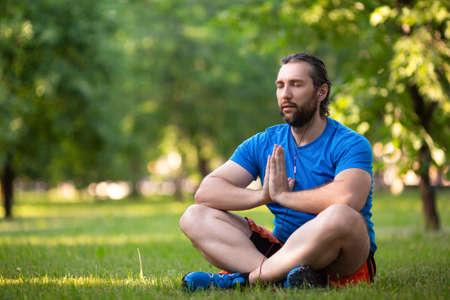Bearded man in lotus pose outdoor. Standard-Bild