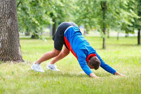 Man practice yoga in park. Adult man do downward facing dog pose.